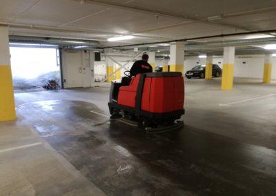 mann rengjør garasje med maskin