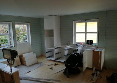 snekker monterer kjøkkeninnredning ved oppussing av bolig