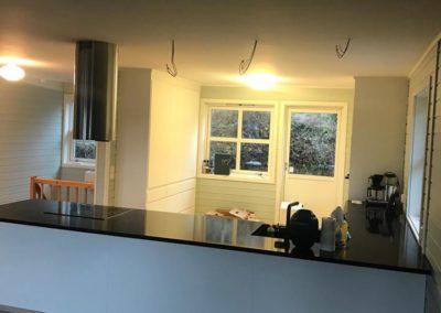 ferdig montert kjøkken med hvite fronter og sort plate